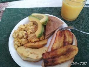 Roasted breadfruit, ackee and cod fish, roti, fried plantain with a slice of hardough bread, avocado slices